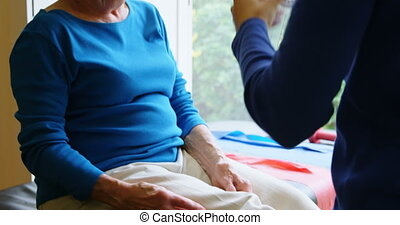 Physiotherapist examining senior woman knee with goniometer...