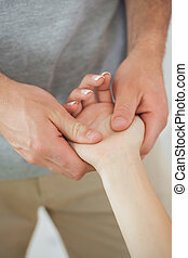 Physiotherapist examining the hand of a patient