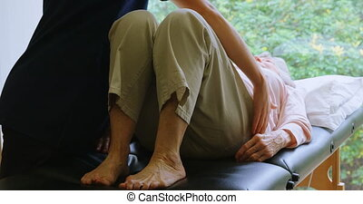 Physiotherapist giving back therapy to senior woman 4k -...
