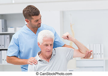 Physiotherapist giving physical therapy to man -...