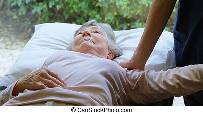 Physiotherapist giving shoulder therapy to senior woman 4k -...