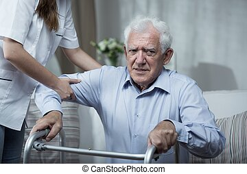 Physiotherapist helping disabled senior man