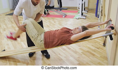 Physiotherapist helping elderly woman rotate legs, doing exercises in fitness room. Healthy gymnastics. Active seniors.