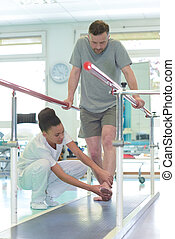 Physiotherapist helping male patient place foot correctly