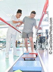 Physiotherapist helping man to walk