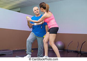 physiotherapist helping senior man to balance