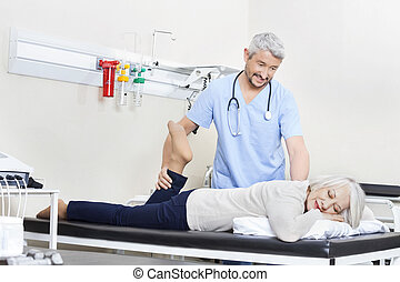 Physiotherapist Helping Senior Patient With Leg Exercise