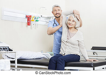 Physiotherapist Helping Senior Woman With Arm Exercise