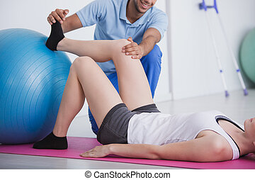 Physiotherapist holding knee and foot of his patient during rehabilitation with a ball