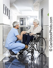 Physiotherapist Holding Senior Woman's Hand On Wheelchair