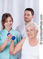 Physiotherapist insuring senior during exercise