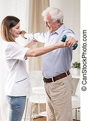 Physiotherapist is helping elder and ill man