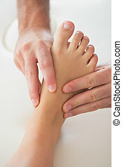 Physiotherapist kneading patients foot in bright office