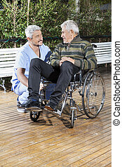 Physiotherapist Looking At Disabled Senior Man In Wheelchair