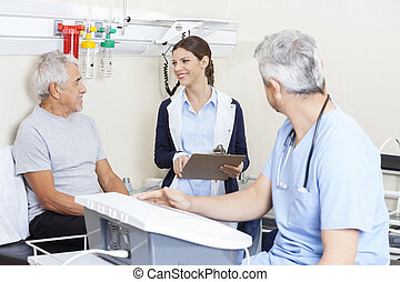 Physiotherapist Looking At Senior Patient In Rehab Center