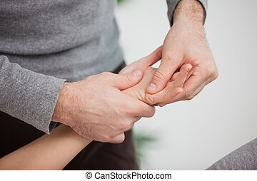 Physiotherapist massaging a hand indoors