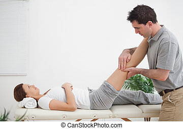 Physiotherapist massaging a leg while placing it on his shoulder in a room
