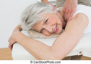 Physiotherapist massaging a senior woman's shoulder - Male...