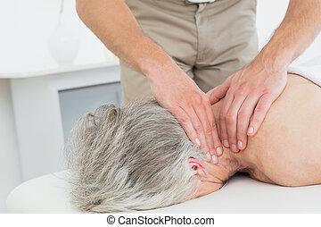 Physiotherapist massaging a senior woman's neck