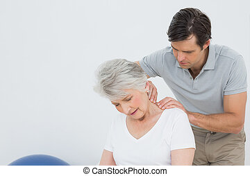 Physiotherapist massaging a senior woman's neck