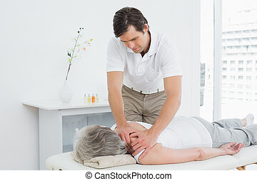 Physiotherapist massaging a senior woman's shoulder