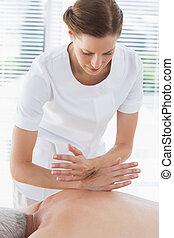 Physiotherapist massaging back of senior man