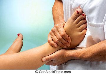 Physiotherapist massaging human foot