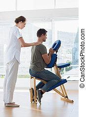 Physiotherapist massaging man in ho