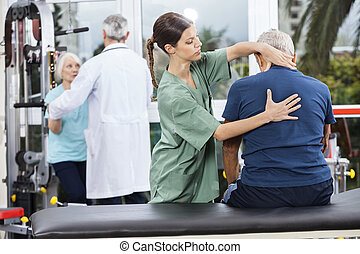 Physiotherapist Massaging Senior Man's Back