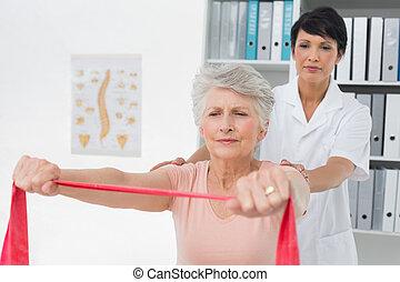 Physiotherapist massaging senior womans back