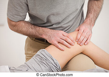 Physiotherapist massaging the knee of a woman