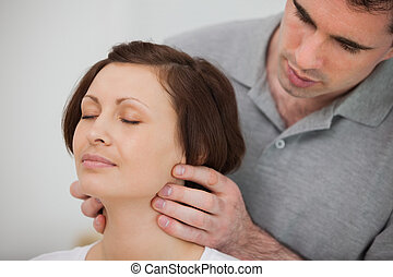 Physiotherapist massaging the neck of a patient in a room