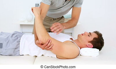 Physiotherapist moving patients injured shoulder in his...