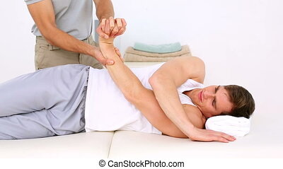 Physiotherapist moving patients injured wrist in his office...