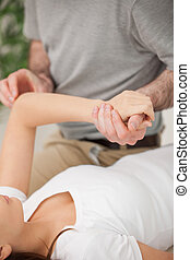 Physiotherapist moving the arm of a woman in a room