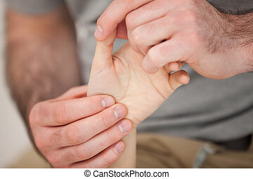 Physiotherapist palpating the fingers of a patient