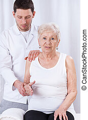 Physiotherapist practicing with elder woman