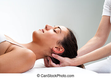 Physiotherapist pressing back of womans head. - Close up of...