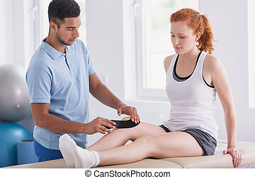 Physiotherapist putting tapes on patient's leg during kinesiotaping