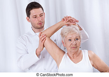 Physiotherapist rehabilitating elderly woman - Vertical view...