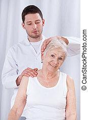 Physiotherapist rehabilitating woman