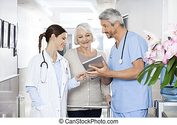 Physiotherapist Showing Reports To Patient And Doctor On Tablet