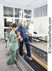 Physiotherapist Standing By Patient Walking Between Parallel Bar