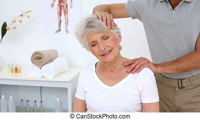 Physiotherapist stretching senior patient