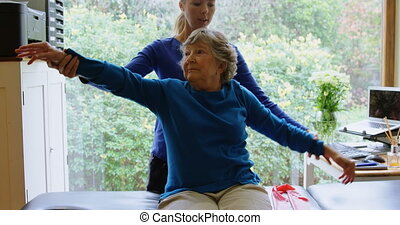 Physiotherapist stretching senior woman shoulder 4k -...