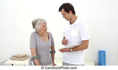 Physiotherapist talking with senior patient on crutches at...