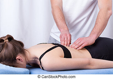 Physiotherapist touching muscle of the back