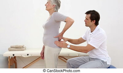 Physiotherapist touching senior patients lower back at the...