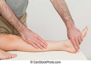 Physiotherapist touching the calf and the foot of a patient