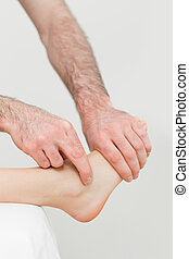 Physiotherapist touching the foot of a patient